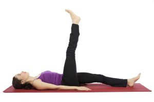 Young woman is doing leg raising exercises.